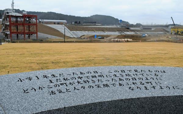 西條さんのメッセージが刻まれた祈念碑。左は旧防災対策庁舎(17日、宮城県南三陸町)