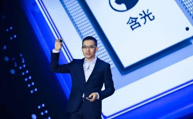 中国・杭州市で開かれたクラウドコンピューティングの会議で最新のAI半導体を公表するアリババCTOの張建鋒氏=ロイター