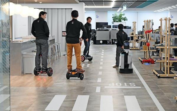 一周200メートルの室内では立ち乗り型電動二輪車ウィングレットやセグウェイを使い移動する(17日、東京都中央区)