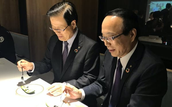 アボカドを試食する宮崎銀行の平野亘也頭取(左)と原口哲二専務(宮崎銀行本店)