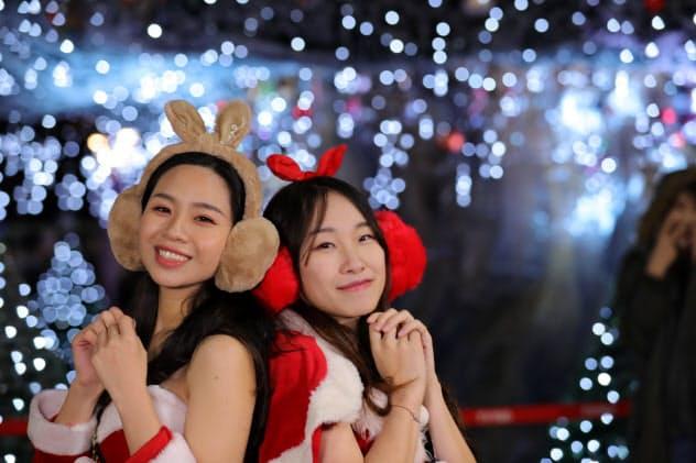 サンタクロースの衣装でカメラに向かってポーズを取ってくれた陳さん(左)=台湾・新北市