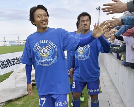 J3昇格を決めサポーターとタッチするFC今治の橋本英郎(左)と駒野友一(11月10日)=共同