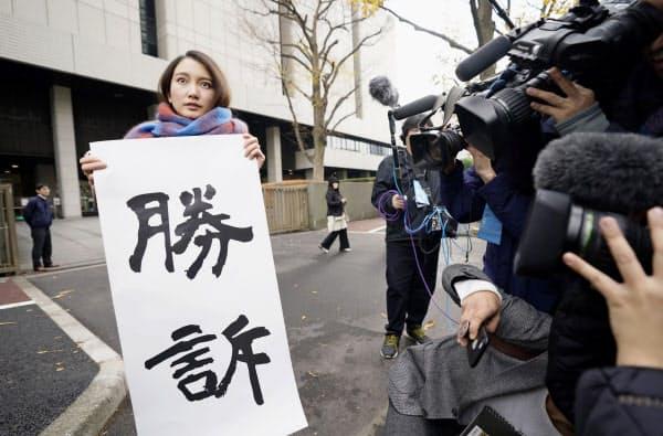 性暴力被害を巡る訴訟の判決後、東京地裁前で「勝訴」と書かれた紙を掲げるジャーナリストの伊藤詩織さん(18日午前)=共同