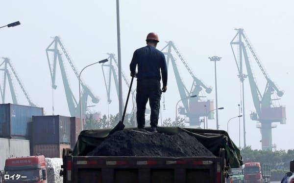 アジアの新興国で石炭需要が増え続ける(中国の港湾近くで石炭を荷積みする労働者)=ロイター