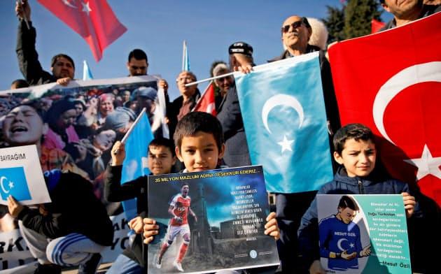 14日、イスタンブールでエジル選手の写真を掲げて中国に抗議するウイグル人の少年ら=ロイター