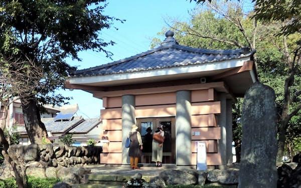 古代の「公文書」とも言える多胡碑をガラス越しに見学する観光客(群馬県高崎市)