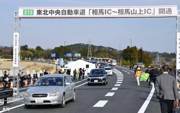 東北中央自動車道の相馬IC―相馬山上IC間の開通記念式典で走行する車両(22日午前、福島県相馬市)=共同