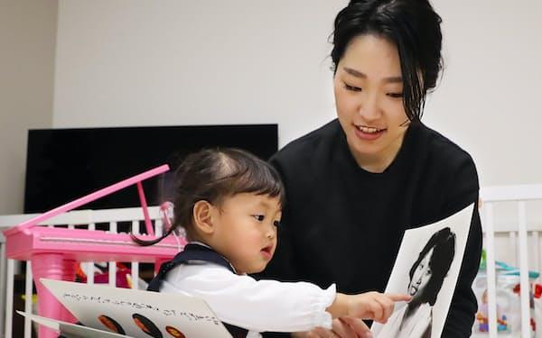 亡くなった母、さつきさんの写真を見る永尾奈津紀さんと長女の美月ちゃん(4日、神戸市東灘区)