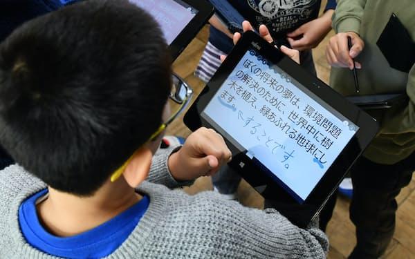 タブレット端末を使い授業を受ける児童