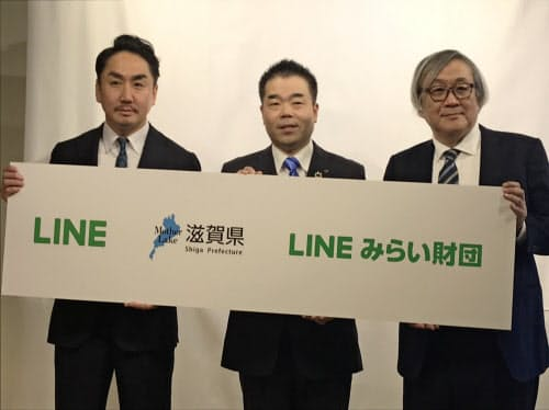 スマート自治体の推進などで連携協定を結んだ滋賀県の三日月大造知事(中)とLINEの出沢剛社長(左)ら(21日、東京・品川のLINE大崎オフィス)