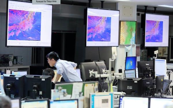 夜間に東京都の天気を予報している気象庁職員