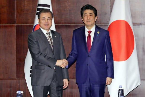 24日、首脳会談で握手する安倍首相と韓国の文大統領(中国・成都)=AP