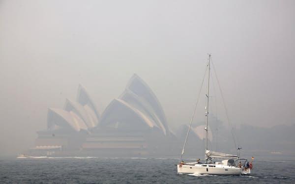 山林火災による煙が広がり、シドニーの観光名所オペラハウスもかすんでみえる=ロイター