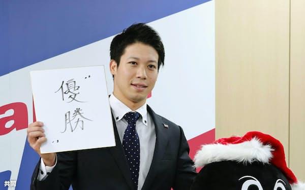 契約更改を終え、来季の目標を書いた色紙を手にポーズをとるヤクルト・山田哲(24日、東京都内の球団事務所)=共同