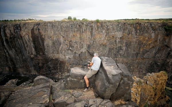 干上がったビクトリアの滝の写真を撮る観光客(4日、ジンバブエ北部)=ロイター
