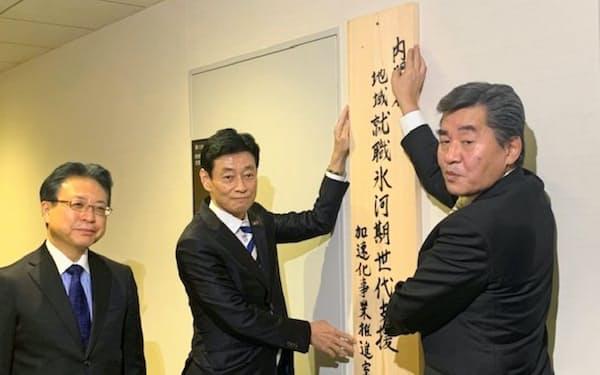 推進室の看板をかける西村経財相(中央)(25日、内閣府)