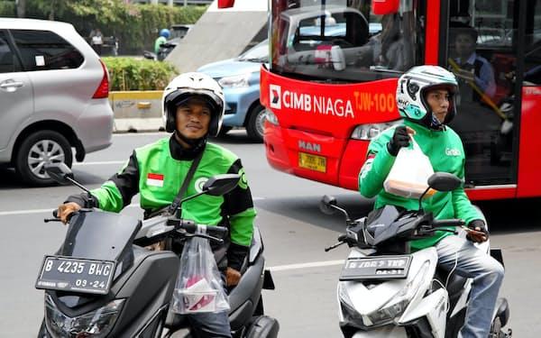 ゴジェックとグラブは配車や宅配で激しい競争を繰り広げている(ジャカルタ中心部のオフィスに外食を届ける両社の運転手)