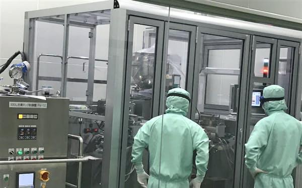 グリーンカプス製薬静岡工場(静岡県富士宮市)稼働に向けてソフトカプセル充填設備を調整する従業員(2019年12月)