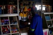 南アフリカ東部のヒルクレストで、停電のなか接客する店員(12月10日)=ロイター