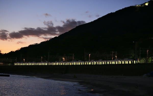 帰宅する人などを乗せ、日暮れ時の須磨浦海岸を走るJR神戸線の列車