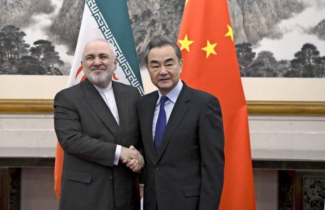 2019年12月、北京で会談する中国の王毅外相(右)とイランのザリフ外相=AP