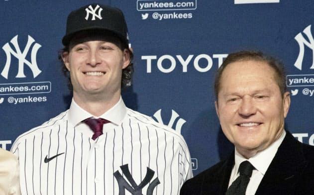 コール(左)が入団会見で袖を通したヤンキースのピンストライプのユニホームの右胸にはナイキのロゴが入っていた=AP