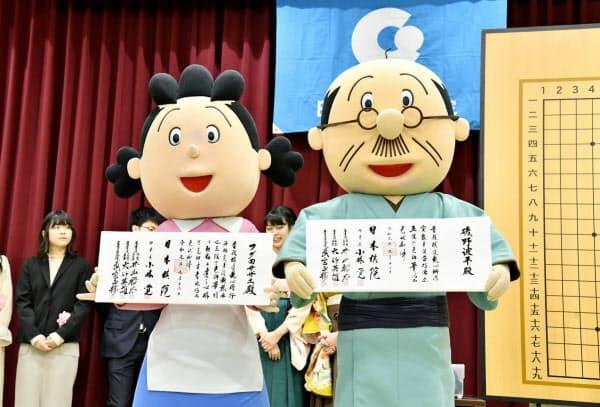 囲碁の打ち初め式で免状を手にする着ぐるみ姿のサザエさん(左)と波平さん(5日、東京都千代田区の日本棋院)=共同