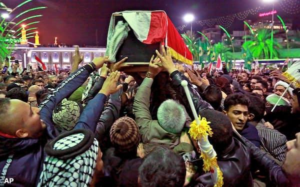 イラン革命防衛隊の精鋭「コッズ部隊」のソレイマニ司令官らのひつぎを運ぶ人々=4日、イラク中部カルバラ(AP=共同)