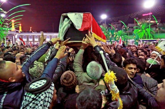 イランは米国による革命防衛隊司令官の殺害に報復を宣言する(ソレイマニ司令官のひつぎを運ぶ人々、イラク中部カルバラ=AP)