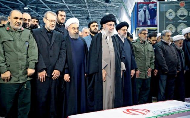 6日、ソレイマニ司令官らのひつぎの前に立つハメネイ師(手前左から4人目)とロウハニ大統領(同3人目)=ロイター
