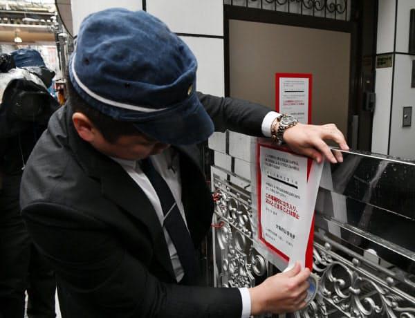 組事務所に標章を張る大阪府警の警察官(7日午前、大阪市中央区)