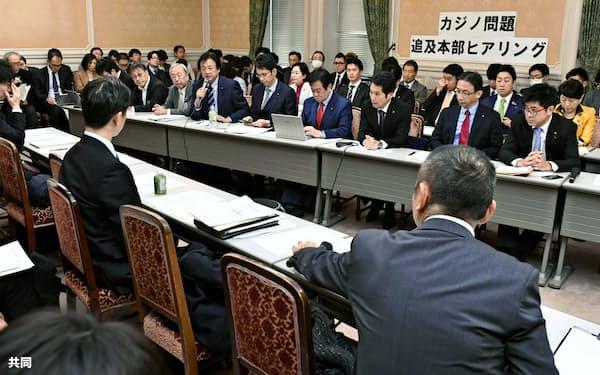 「カジノ問題追及本部」の初会合で、省庁の担当者ら(手前)から聞き取りをする野党議員(7日午前、国会)=共同