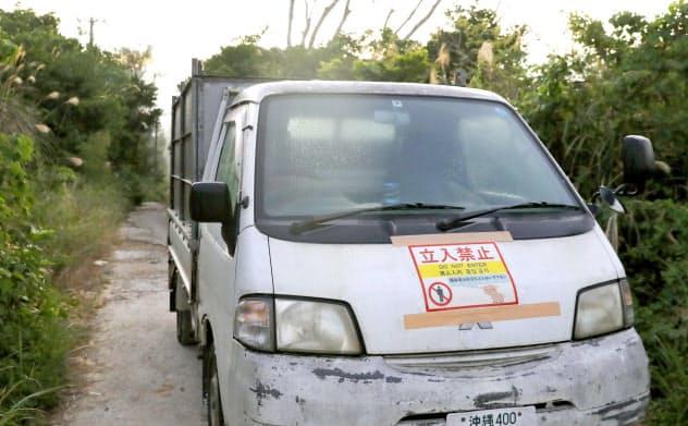豚コレラ発生の疑いがある養豚場付近で、関係者以外立ち入り禁止の張り紙をした車両(8日午前、沖縄県うるま市)=共同