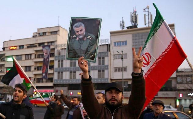 イランによるミサイル発射を祝し、ソレイマニ司令官の肖像を掲げる男性(8日、テヘラン)=ロイター