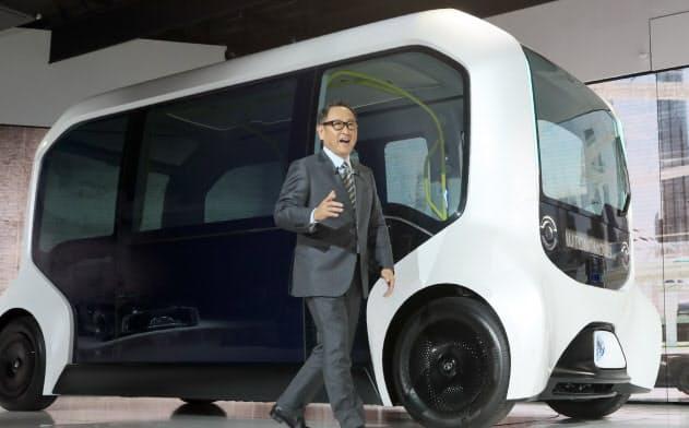 東京モーターショーでスピーチするトヨタ自動車の豊田章男社長と、トヨタが商用向けに開発を進めている自動運転EV「イーパレット」(10月23日、東京都江東区)