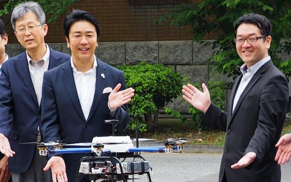 増本CEO(右)は福岡市とのドローン配送実験にも参加(19年5月、福岡市)