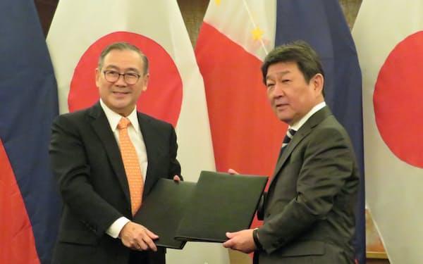 外相会談後の署名式に臨む茂木氏(右)とロクシン氏(9日、マニラ)