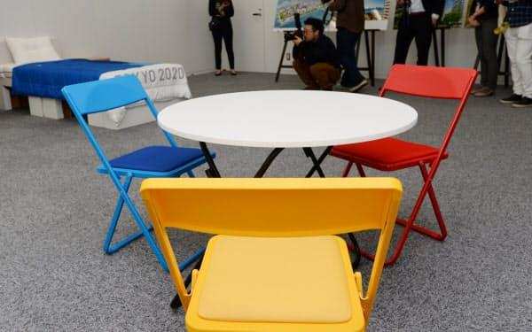 報道陣に公開された五輪選手村の室内に置かれる椅子と丸テーブル。椅子の色は大会をイメージしカラフルだ(9日、東京都中央区)