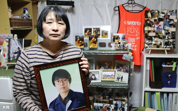 自殺した鈴木雄大さんの遺影を手にする、母親の龍子さん(7日、北海道釧路市)=共同