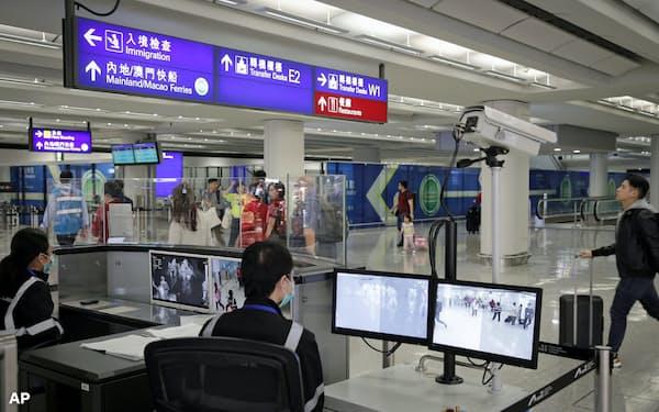 香港国際空港で検査装置を使って旅客の体温を調べる担当者ら(4日、香港)=AP