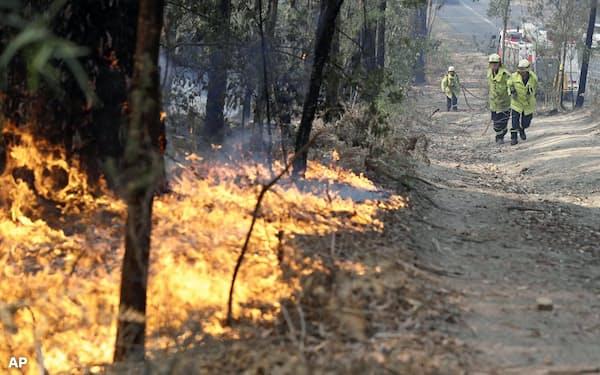 3日、オーストラリア東部ニューサウスウェールズ州で、森林火災の消火に当たる消防士=AP
