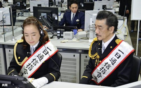 指令センターで110番の受理や無線指令を体験する宇崎竜童さんと阿木燿子さん夫妻(10日午前、警視庁本部)=共同