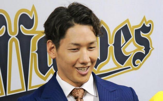昨年11月、契約更改後の記者会見で笑顔を見せる吉田正=共同