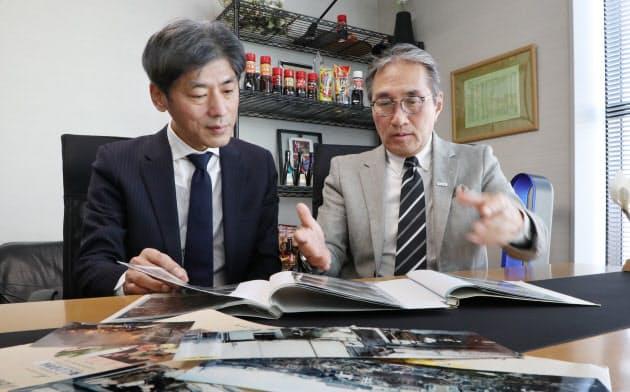 写真を見て震災当時のことを話すオリバーソースの道満雅彦社長(右)と中嶋貞行執行役員(神戸市中央区)