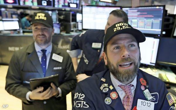 10日のダウ平均は一時、初の2万9000ドル台に乗せた(「ダウ 29,000」の帽子をかぶるニューヨーク証券取引所関係者)=AP