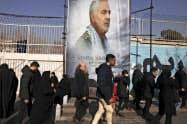 6日、イラン精鋭部隊のソレイマニ司令官の葬儀に参列し、かつての米国大使館前に掲げられた司令官の写真の前を歩く市民=AP