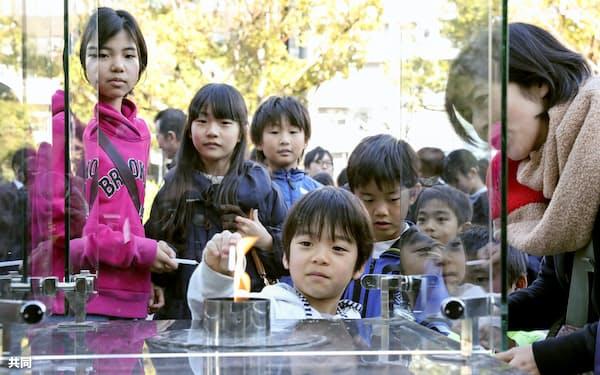 「1.17希望の灯り」の分灯が始まり、ろうそくに火を移す子どもたち(11日、神戸市)=共同