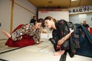 小倉百人一首競技かるたの第64期クイーン位決定戦を前に、かるた取りを披露する山下恵令さん(左)と挑戦者の本多恭子さん(11日、大津市の近江神宮)=共同