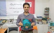 出版した絵本を手にするアフガニスタンのNGO「ガフワラ」創設者ザビーフ・マハディさん(2019年7月、カブール)=本人提供・時事