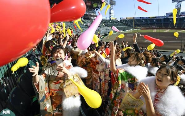甲子園球場で阪神タイガース戦の名物「ジェット風船」を飛ばす新成人たち(13日、兵庫県西宮市)=共同